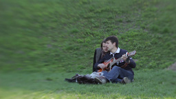 The guy playing for the girls on the guitar while Dating Footage