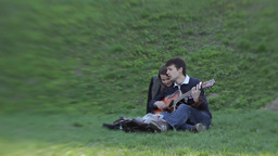 The guy playing for the girls on the guitar while Dating Stock Video Footage