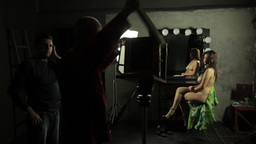 Behind the scenes of erotic photo shoot. Nude model and photographers at work Footage