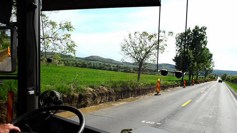 View through the windshield of a truck or bus while it runs on a paved road bord Footage