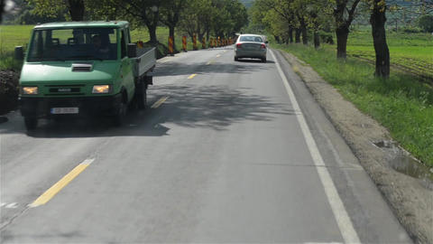 View through the windshield of a truck or bus while it runs on a paved road 2 Footage
