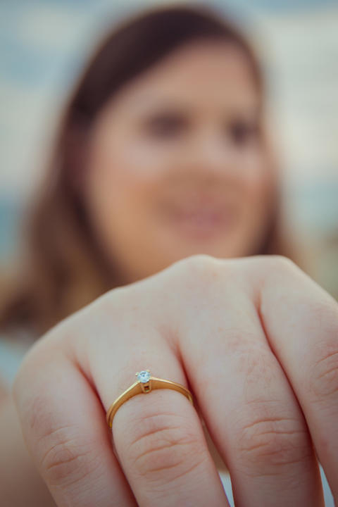 Happy woman shows off her new engagement ring on her finger フォト