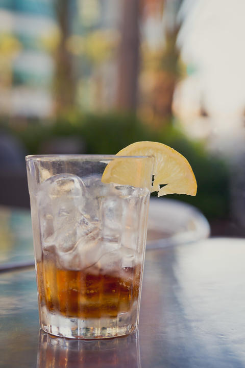 Glass with cola, ice and lemon on a table outside Foto