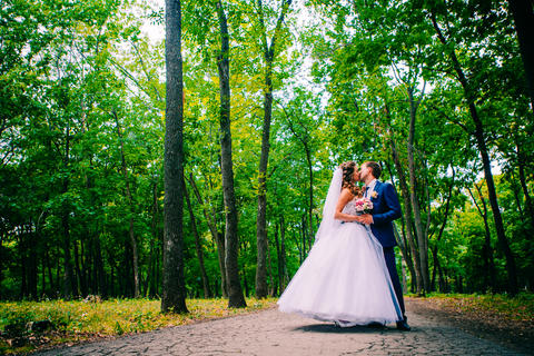 beautiful young couple posing in the park on a background of trees Photo