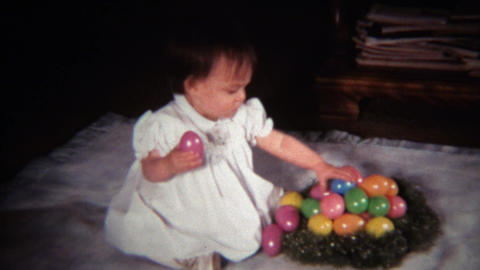 1971: Baby girl sulking with plastic Easter egg nest Footage