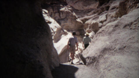 1971: Hikes walking on dry trail rocky smooth cavern cliffs Footage