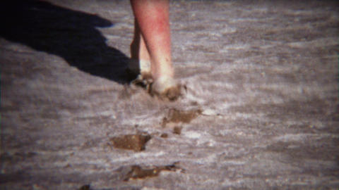 1971: Shoes walking through thick mud on dry lake bed Footage