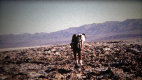 1971: Man walking across mountainous dry lake bed with backpack Footage