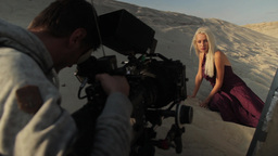 The cameraman shoots the actress lying on the sand in the desert Footage
