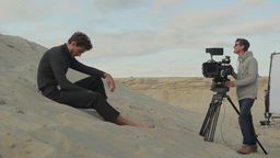 The cameraman shoots the actor in the desert during the day Footage