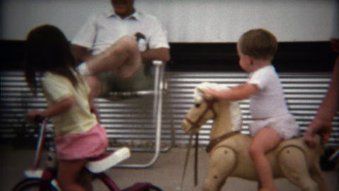 1971: Toddler boy riding toy horse with help from parent pushing Footage