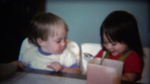 1971: Baby siblings sharing food from square plastic tupperware bowl Footage