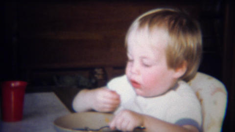 1971: Cute blonde boy eating pasta with hands and spoon in bowl Footage