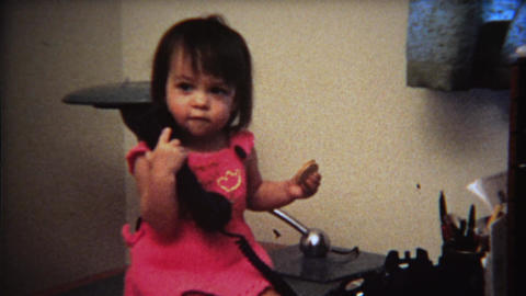 1971: Cute toddler girl playing with telephone on office desk Footage