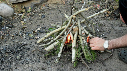 Male trying to Light a small campfire with a kindling Footage