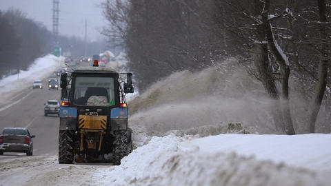 Tractors of road service clean up the snow from the roadside Footage