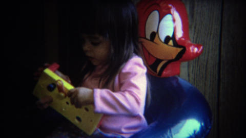 1971: Girl solves puzzle in woody woodpecker inflatable chair Footage