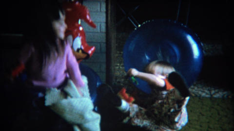 1971: Cute kids bounce on woody woodpecker inflatable chairs Footage