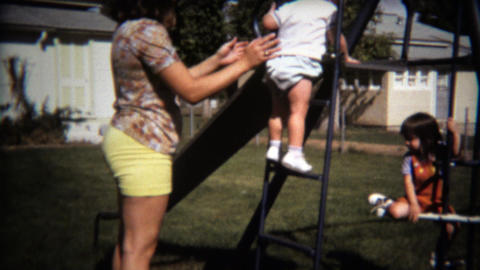 1971: Baby boy and sister sliding on backyard playground jungle gym Footage