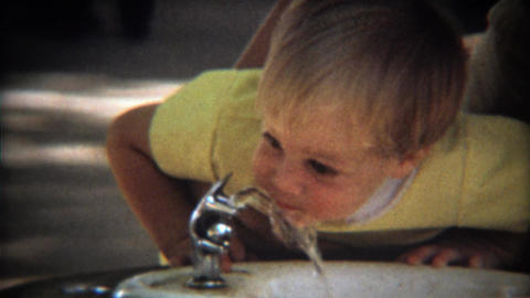 1971: Toddler's 1st drink of water from public park fountain Footage