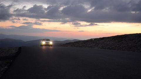 Car running on a paved road in the evening down on a mountain road 115 Footage