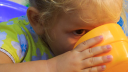 Closeup Small Blonde Girl Drinks From Yellow Cup stock footage