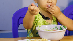 closeup little blonde girl eats soup vegetables Footage