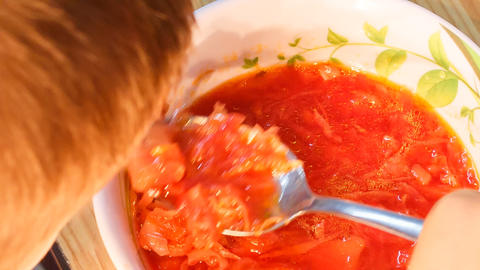 closeup boy eats Ukrainian national soup borsch Footage