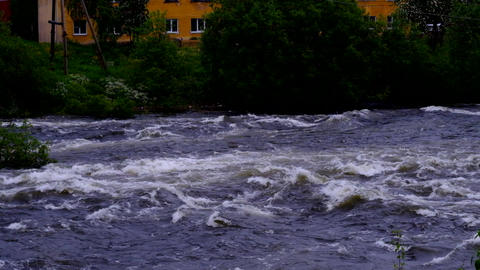 A stormy river runs past the yellow house Image