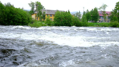 A stormy river runs past the yellow house Filmmaterial
