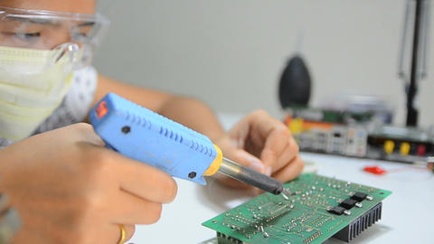 Dolly slider Technician is soldering to the electronic print circuit board 001 Footage