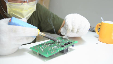 Technician is soldering to the electronic print circuit board 004 Footage