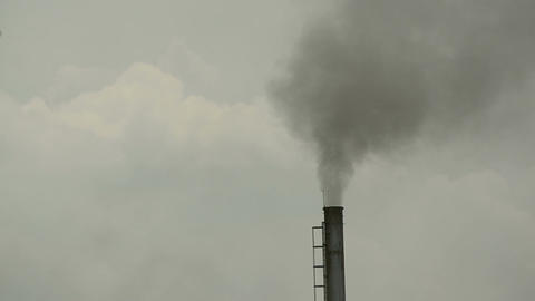 The industrial chimney is emitting exhaust fumes that pollute the environment ag Footage