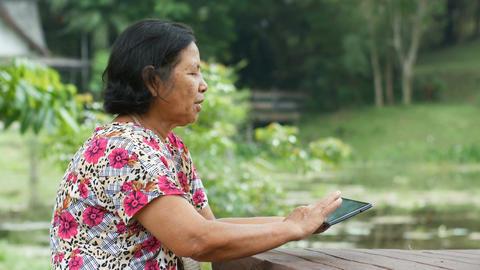 Thai Senior Woman Using Tablet In Garden Footage