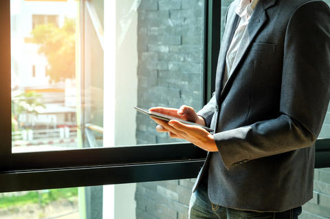 Business concepts,Businessmen are using a tablet in the office window フォト