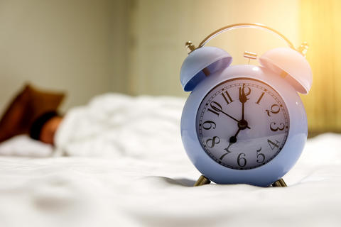 Alarm clock put on the table in the bedroom set at 7:00 AM,Behind people sleepin Fotografía