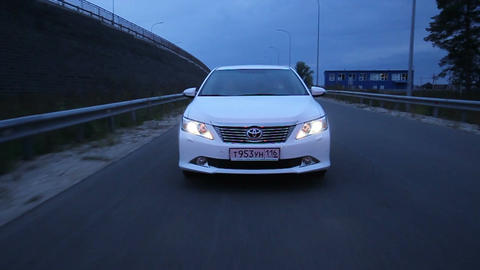 Front View Toyota with Switched on Lights Drives along Road Footage