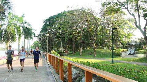 Cycling and walking in Benchakitti Park Bangkok city Thailand ビデオ