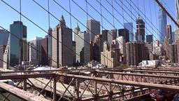 USA New York City Manhattan skyline seen through steel cables of Brooklyn Bridge Footage