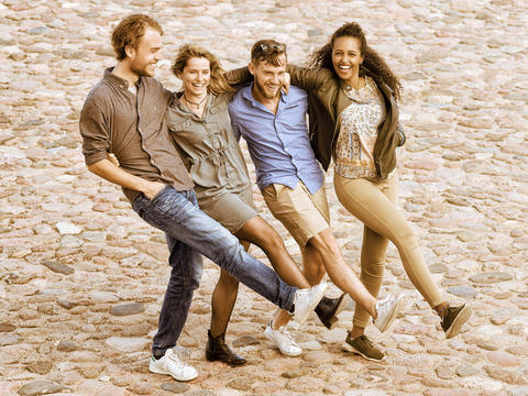 Group of smiling young multiracial friends trying to move legs Foto