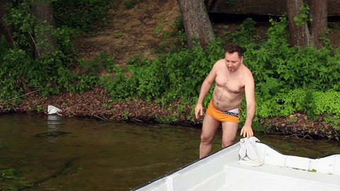 Average, fat male taking off his shirt - outdoor, lakeside ビデオ