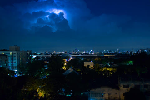 Storm clouds with lightning strike bolts passing over night city フォト