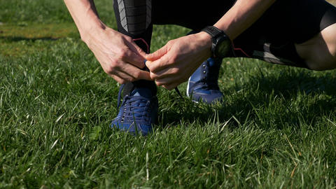 Closeup of athlete man tying shoelaces before jogging in the park Footage