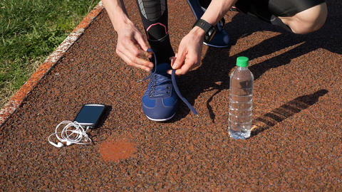 Jogger with smartwatch tying shoelaces and picking up smartphone with earphones  Footage