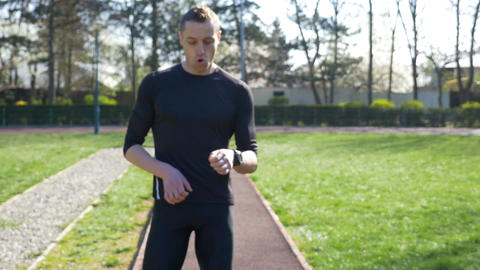 Fit man jogger stopping for break and catching breath to check race time on smar Footage