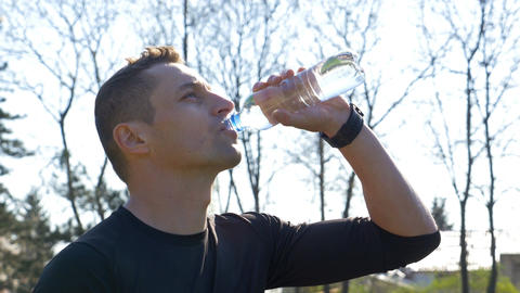 Closeup of young thirsty athlete drinking water from bottle after workout Footage