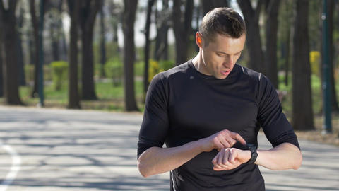 Closeup of fit jogger stopping from running in park checking smartwatch fitness  Footage