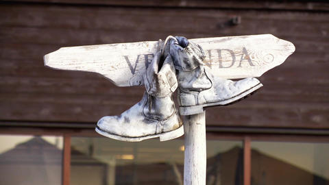 Pair of old white boots hang on a wooden nameplate and wiggle in summer day Footage