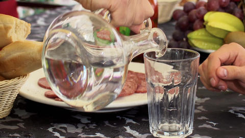 Man hand pours vodka from a decanter to a glass and another hand take a glass Footage