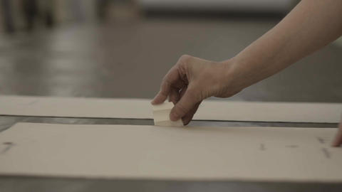Worker encircle cardboard by a piece of chalk in furniture factory Footage